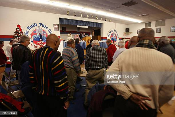 Retired members of the United Auto Workers pray for a better economic climate while attending a monthly benefits meeting November 20, 2008 in...