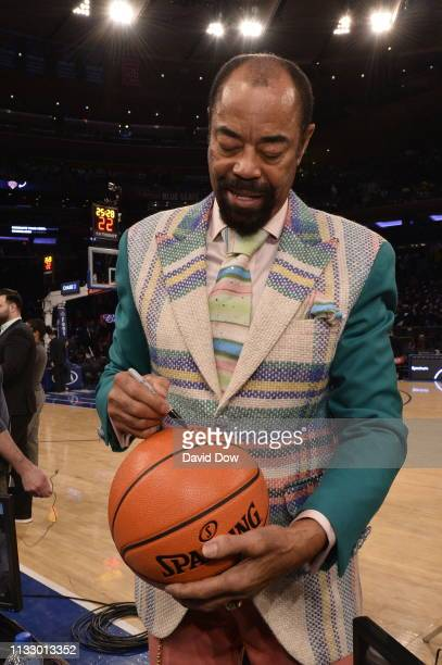 Retired NBA Player Walt Frazier signs a basketball before the game between the Los Angeles Lakers and the New York Knicks on March 17, 2019 at...