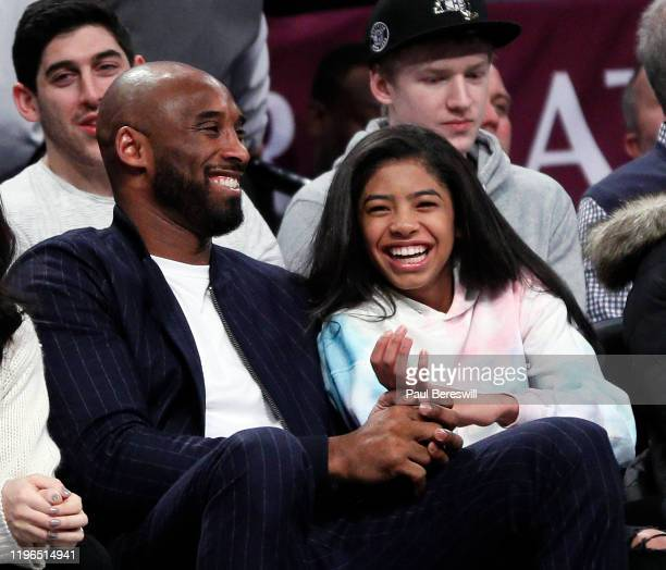 Retired NBA star Kobe Bryant and his daughter Gigi watch an NBA basketball game between the Brooklyn Nets and Atlanta Hawks on December 21 2019 at...