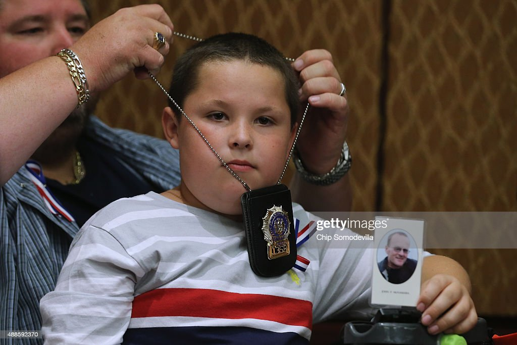 Retired New York Police Detective Kenny Anderson hangs his badge on his son Christopher Anderson, 10, as he holds a photograph of deceased 9/11 responder Jonathan McNamara during a news conference to demand that Congress pass an extension of the Zadroga 9/11 health bill at the U.S. Capitol September 16, 2015 in Washington, DC. Firefighter McNamera worked more than 500 hours at Ground Zero and died in August 2009 of cancer at the age of 44. Comedian and former Daily Show host Jon Stewart joined ailing police and firefighters in lobbying Congress for a permanent extension of the Zadroga Act's $1.6 billion health and monitoring effort for the 72,000 emergency responders who worked at Ground Zero.