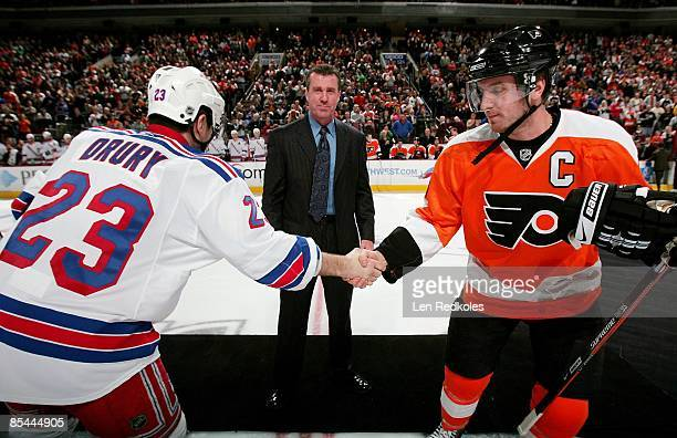 Retired NHL Linseman Pat Dapuzzo stands center during a jersey presentation as Mike Richards of the Philadelphia Flyers shakes hands with Chris Drury...