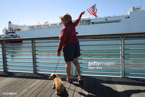 Retired nurse Donna waves an American flag toward the USNS Mercy Navy hospital ship after it arrived in the Port of Los Angeles to assist with the...