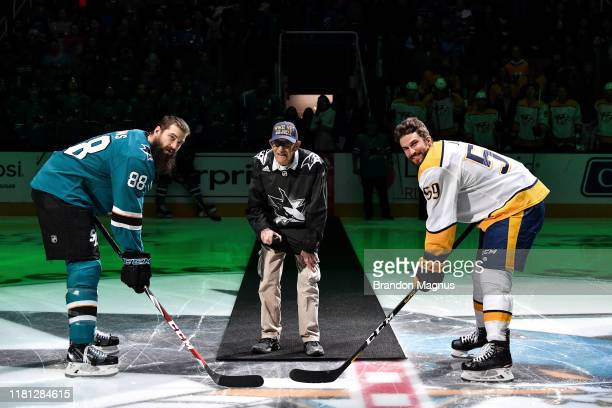 Retired Petty Officer Second Class Frank Ganz drops the puck on Military Appreciation Night in front of Brent Burns of the San Jose Sharks and Roman...