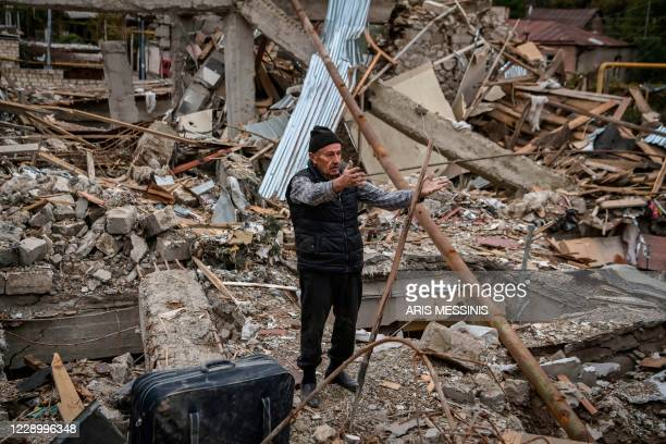 Retired police officer Genadiy Avanesyan searches for belongings in the remains of his house, which is said was destroyed by Azeri shelling, in the...