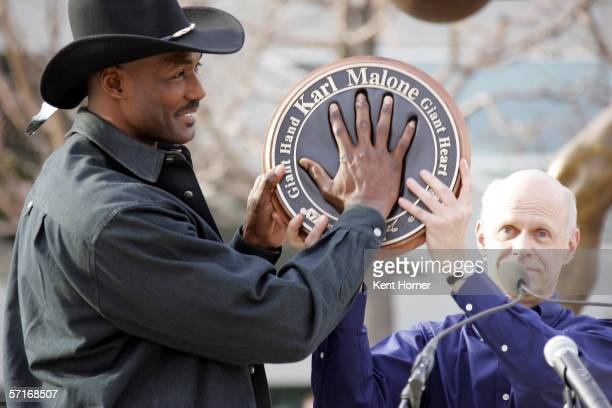 Retired powerfoward Karl Malone fits his hand into a mold at the unveiling of the statue commissioned by the Utah Jazz owner Larry H Miller on March...