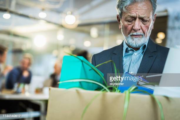 retired senior businessman leaving the office with his belongings. - downsizing unemployment stock pictures, royalty-free photos & images