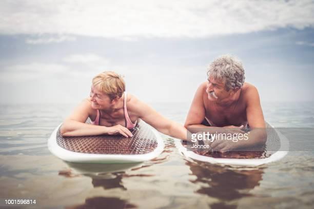 ancien couple de personnes âgées bénéficiant de la journée sur la mer - aventure photos et images de collection