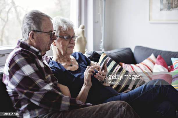 retired senior couple sharing smart phone sitting on sofa in living room at home - 70 79 years stock pictures, royalty-free photos & images