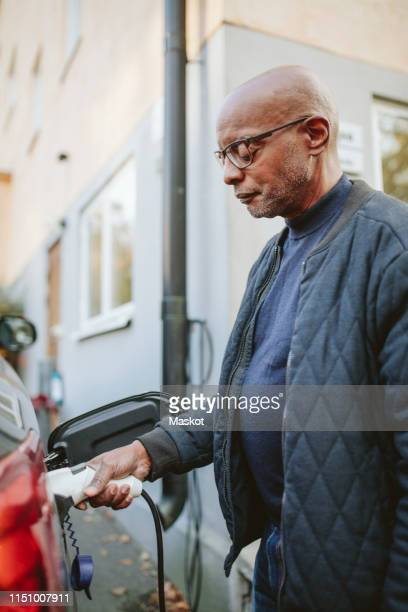retired senior man charging electric car outside house - plugging in stock pictures, royalty-free photos & images