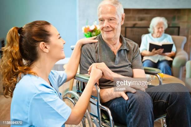 homem sênior aposentado que olha a enfermeira fêmea de sorriso - izusek - fotografias e filmes do acervo