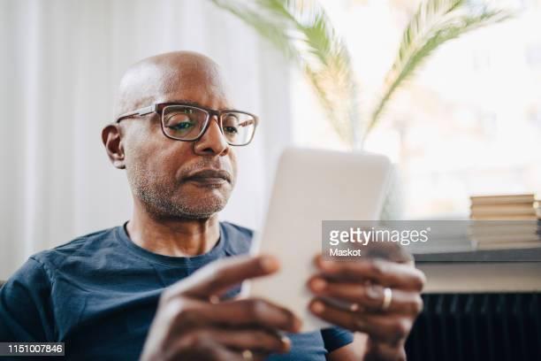 retired senior man reading e-book in room at home - alleen seniore mannen stockfoto's en -beelden