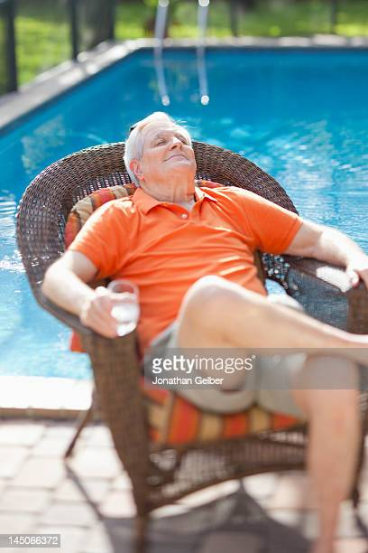 A retired senior man relaxing in the sun next to a pool