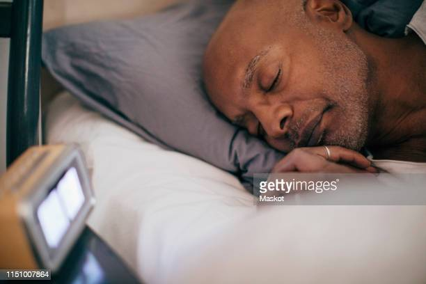 retired senior man sleeping on bed by alarm clock at home - sleep stock pictures, royalty-free photos & images