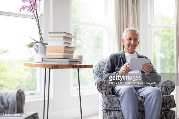 retired senior man surfing on digital tablet - surfing the net stock pictures, royalty-free photos & images