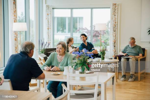 retired senior men and women sitting with male nurse at elderly nursing home - retirement community stock pictures, royalty-free photos & images