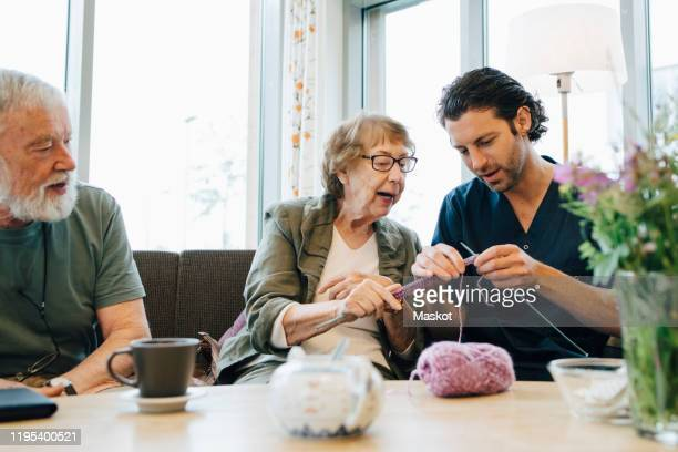 retired senior woman teaching knitting to male nurse while sitting on sofa at elderly care home - knitting stock pictures, royalty-free photos & images