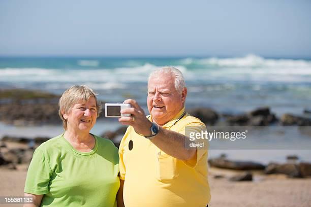 pensionierte senioren nimmt ein selbstporträt am strand - dicke frauen am strand stock-fotos und bilder
