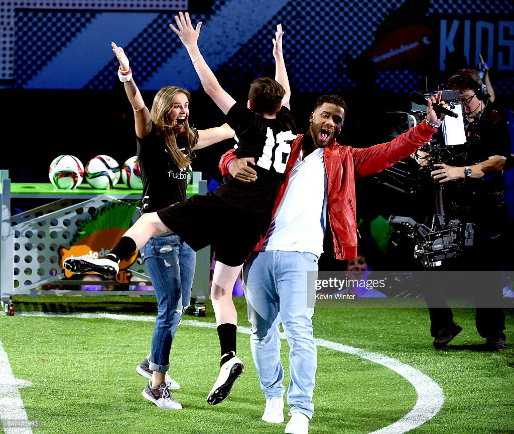 Retired soccer player Brandi Chastain, $50K Triple Shot contestant Oliver Callanan, and host Russell Wilson react during a contest onstage during the Nickelodeon Kids' Choice Sports Awards 2016 at UCLA's Pauley Pavilion on July 14, 2016 in Westwood, California. The Nickelodeon Kids' Choice Sports Awards 2016 show airs on July 17, 2016 at 8pm on Nickelodeon.
