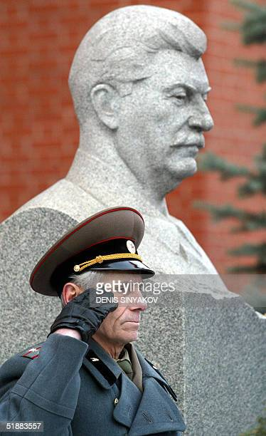 Retired Soviet officer salutes standing in front of the Stalin tomb next to the Kremlin wall in Moscow during the Soviet leader's birthday...