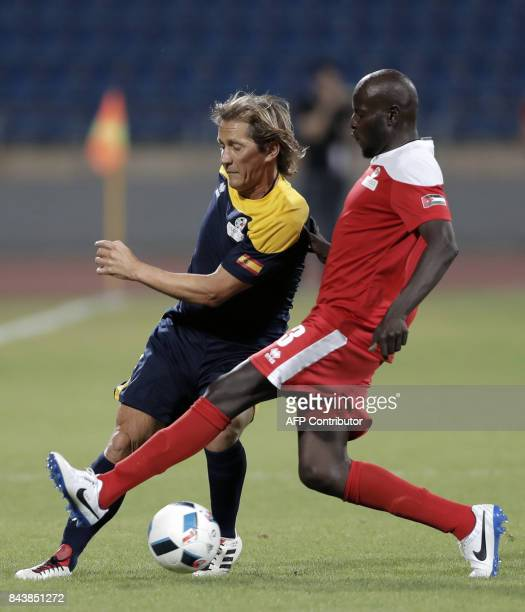 Retired Spanish former football player Michel Salgado vies for the ball against a retired Jordanian football star during a friendly match organised...
