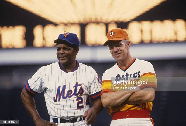 Retired stars Willie Mays of the New York Mets and Bill Virdon stand on a field during the 1980s