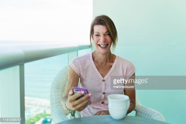 """retired trans woman having a coffee on balcony. - """"martine doucet"""" or martinedoucet fotografías e imágenes de stock"""