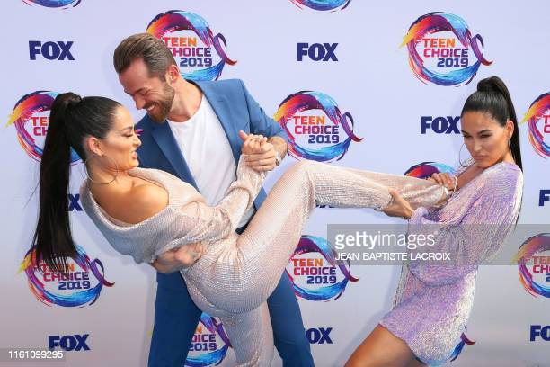 Retired US wrestlers Nikki Bella and Brie Bella and RussianUS dancer Artem Chigvintsev attend the 2019 Teen Choice Awards in Hermosa Beach California...
