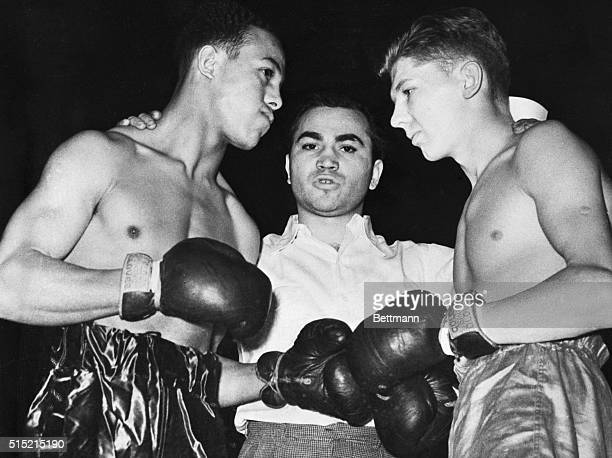 Retired welterweight and lightweight champion Barney Ross referees Lorenzo Nelson and Erwin Bielowski in the Golden Gloves Tournament