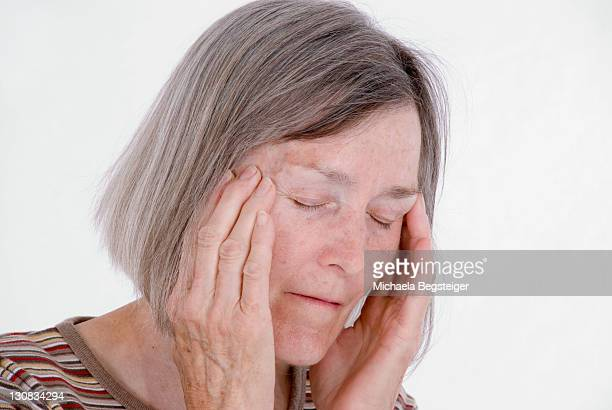 retired woman, 65 years old, with a headache - 65 69 years stock pictures, royalty-free photos & images