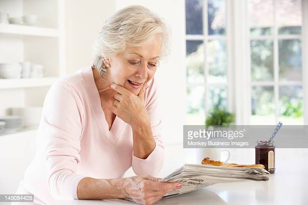 retired woman eating breakfast - monkey eating paper stock pictures, royalty-free photos & images
