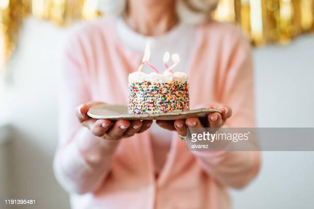 gâteau rechargé de femme à la retraite avec des bougies d'anniversaire - birthday photos et images de collection
