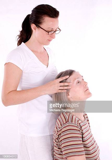 retired woman, older than 60 years, getting a head massage - 65 69 years stock pictures, royalty-free photos & images