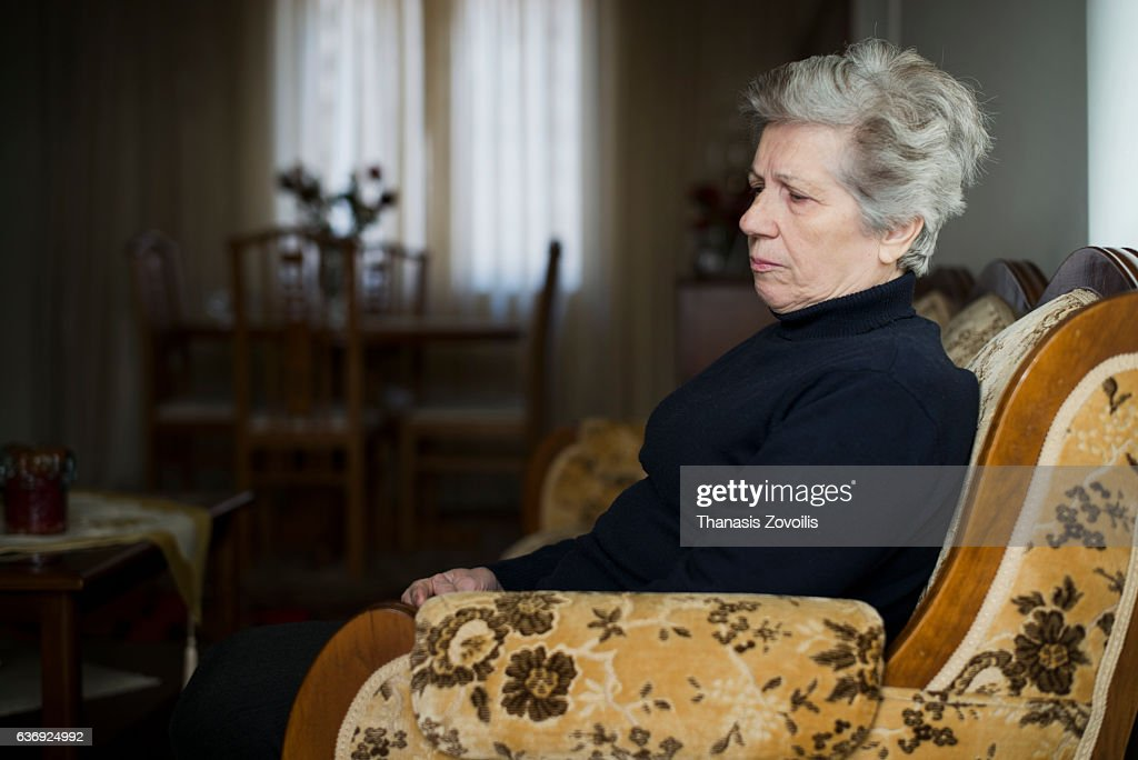 Retired woman relaxing in living room : Stock Photo