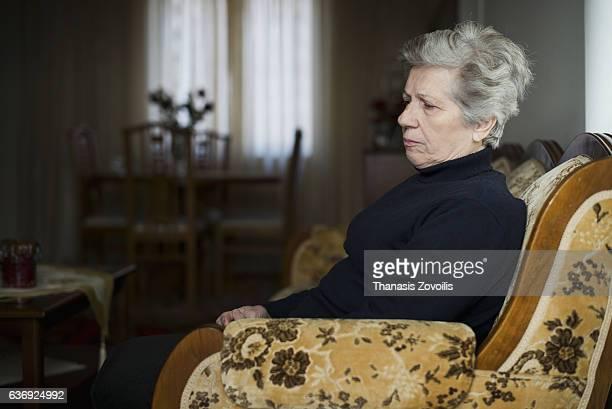 retired woman relaxing in living room - einfaches leben stock-fotos und bilder