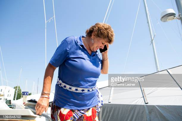 retired woman talking on phone in dry dock on a summer day in maine. - catherine ledner stock pictures, royalty-free photos & images