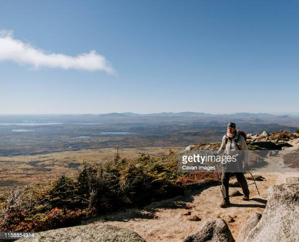 a retirement aged hiker walks along the appalachian trail in maine - appalachian trail stock pictures, royalty-free photos & images