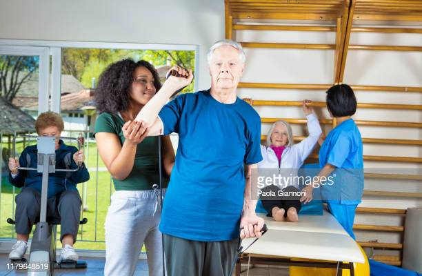 retirement community. group of elderly people assisted by physiotherapists in the retirement community gym at recovery time - active lifestyle stock pictures, royalty-free photos & images
