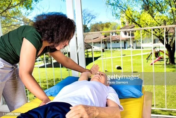 rentengemeinde. physiotherapeut hilft älteren mann beim dehnen in der rentnerhalle - turner syndrome stock-fotos und bilder