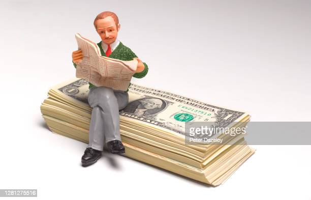 Retirement illustrated with figurine sitting on paper currency, studio London, October 2020