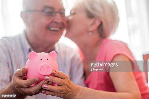 Retirement savings for senior couple, holding piggy bank