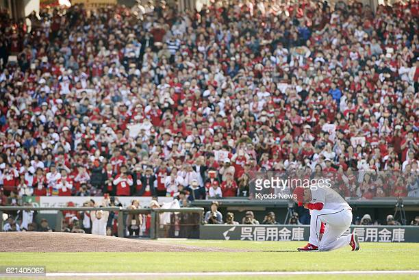 Retiring Hiroshima Carp righthander Hiroki Kuroda sinks to his knee on the field at Mazda Stadium during his retirement ceremony in the western Japan...