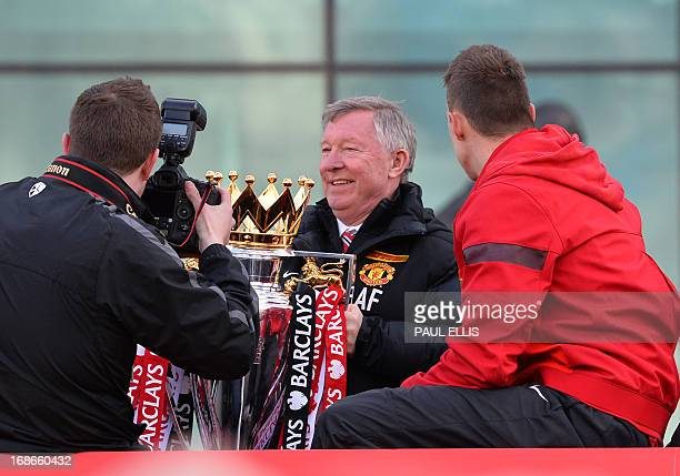 Retiring iconic Manchester United manager Alex Ferguson holds the Premier League trophy as he boards the champions' bus outside Old Trafford Stadium...
