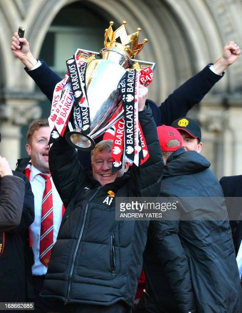 Retiring iconic Manchester United manager Alex Ferguson holds the Premier League trophy outside the town hall in Manchester north west England on May...
