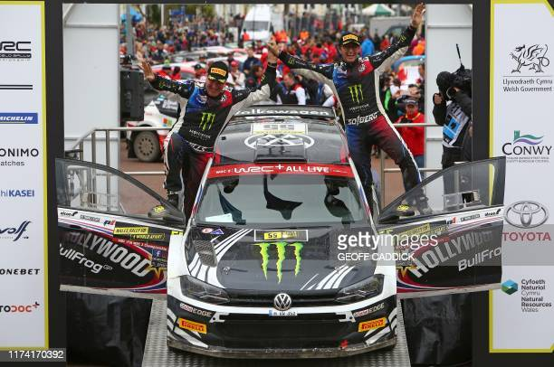 Retiring Norwegian pilot Petter Solberg and copilot Phil Mills stand with their car and wave to fans from the podium at the end of the Wales Rally GB...