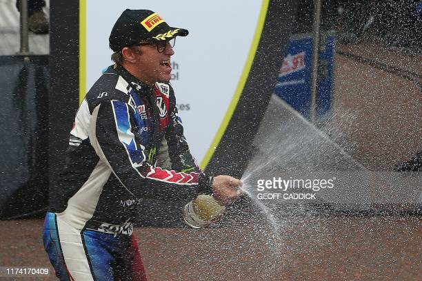 Retiring Norwegian pilot Petter Solberg sprays champagne after waving to rally fans at the end of the Wales Rally GB the 12th round of the FIA World...