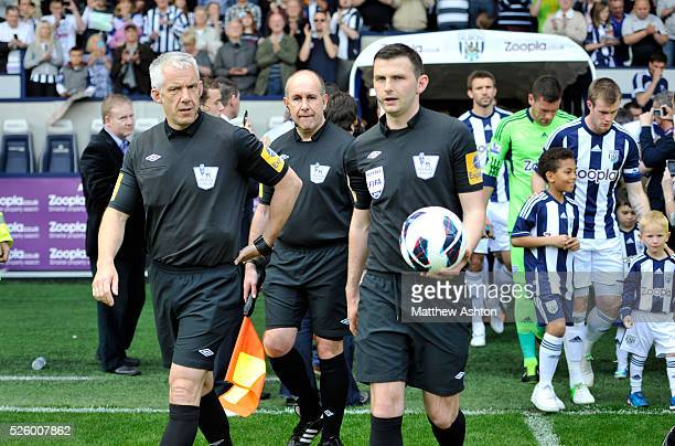 retiring official assistant referee Ceri Richards walks onto the pitch with officials for the match Michael Oliver referee fourth official Chris Foy
