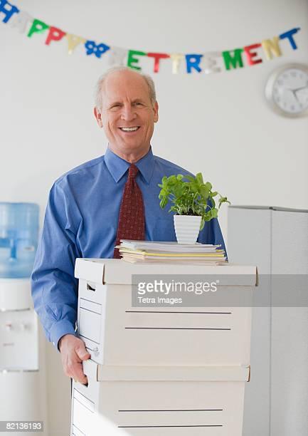 Retiring senior businessman carrying boxes