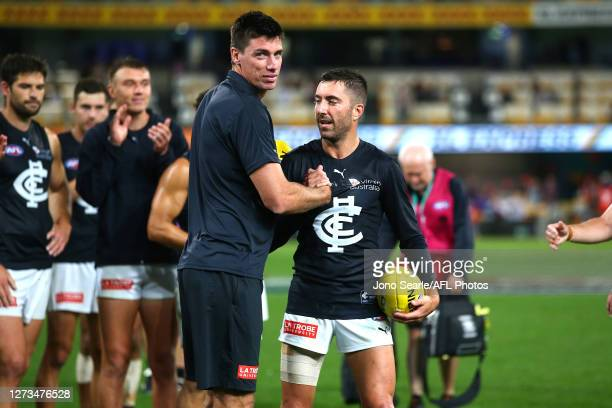 Retiring team mates Matthew Kreuzer and Kade Simpson are clapped off the ground after the round 18 AFL match between the Brisbane Lions and the...