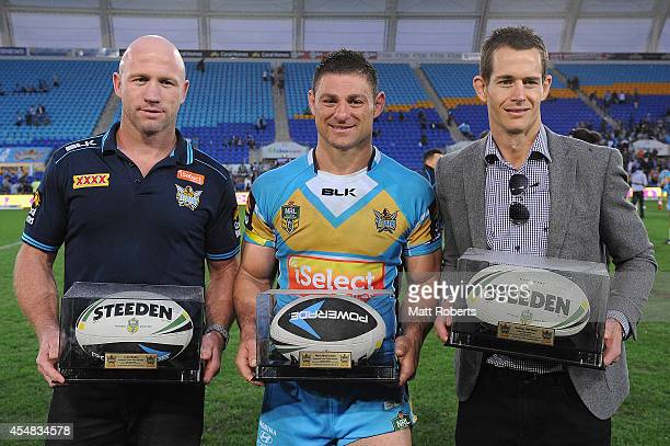 Retiring Titans players Luke Bailey Mark Minichiello and Ashley Harrison pose for a photograph after the round 26 NRL match between the Gold Coast...