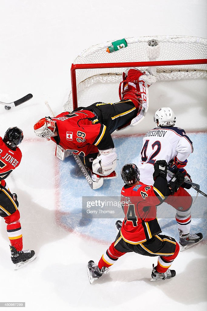 Reto Berra #29 and Chris Butler #44 of the Calgary Flames defend the net in a game against Artem Anisimov #42 of the Columbus Blue Jackets at Scotiabank Saddledome on November 20, 2013 in Calgary, Alberta, Canada.